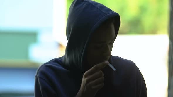 Hooded black male teenager secretly smoking, hiding from parents