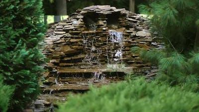 A small decorative waterfall in the  garden. Landscape design