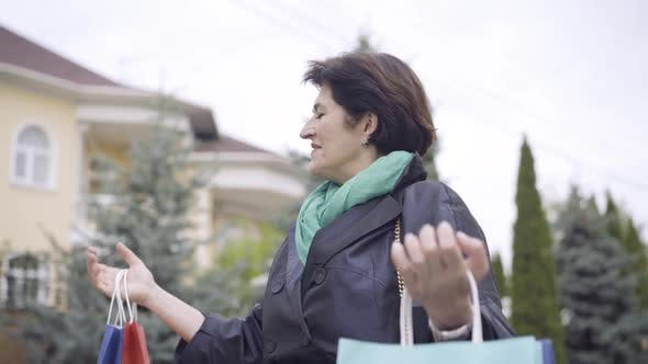 Thumbnail for Happy Female Shopper Standing Outdoors Raising Hands with Shopping Bags and Smiling