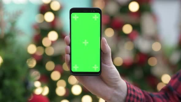 Thumbnail for Hand Of Young Man Using Phone With Green Screen Against Christmas Trees Outdoors
