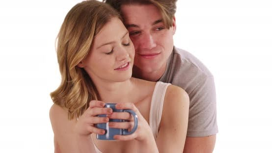Male hugging girlfriend with coffee mug from behind on white background
