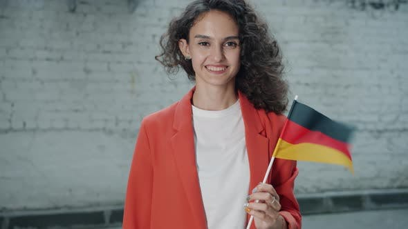 Slow Motion Portrait of Attractive Mixed Race Woman Holding German Official Flag Standing Outdoors