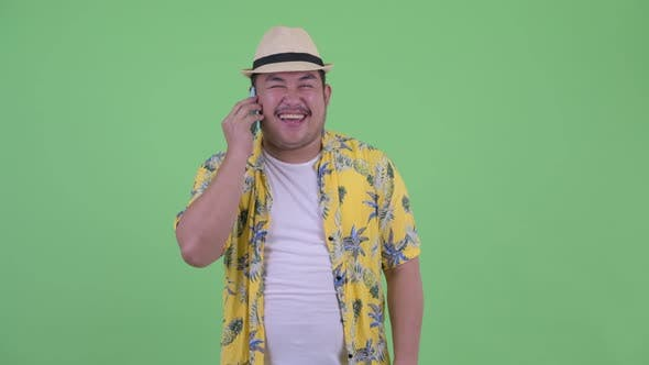 Thumbnail for Happy Young Overweight Asian Tourist Man Talking on the Phone
