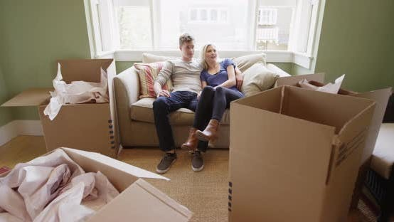 Thumbnail for Happy couple sitting on couch after unpacking