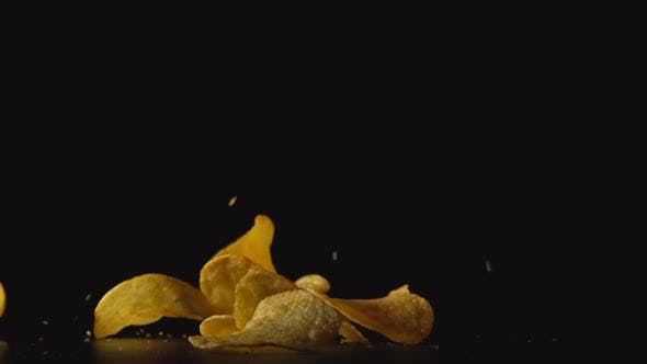 Thumbnail for А Lot Of Potato Chips Fall On A Table. Black Background