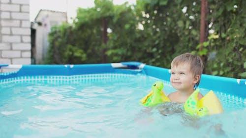 Kid in Oversleeves Swims in the Pool in the Yard