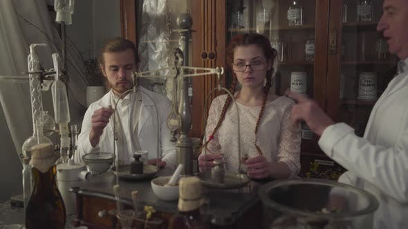Thumbnail for Portrait of Three Caucasian Apothecaries Talking, People Standing in Ancient Drugstore with Test