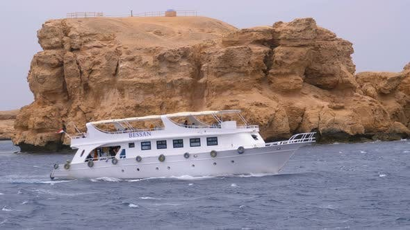 Thumbnail for Pleasure Boat with Tourists Sails in the Stormy Sea on the Background of Rocks. Egypt