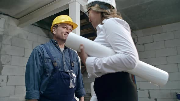 Thumbnail for Female engineer in hard hat holding blueprints and talking to mature foreman