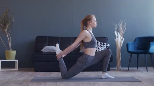Young Woman Stretching Her Legs, Practicing Pilates at Home