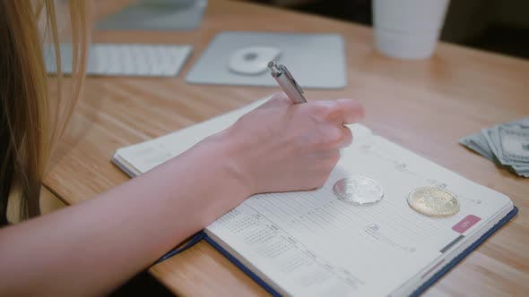Thumbnail for Woman with Bitcoins Writing Into Daily Planner. Crop View of Female with Pen Writing Data in Daily