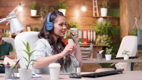 Woman Listens Music, Dances and Starts Singing at the Office