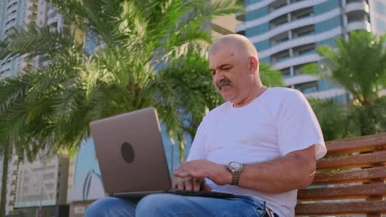 Thumbnail for Senior Man Sitting in Park with Palm Trees with Laptop in Summer Checks Bank Account