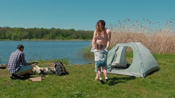 Family is Resting on the Bank of the River with a Tent