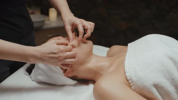 Thumbnail for Brunette Woman Receiving Facial Massage in Spa Relaxing on Massage Table Wellness Body and Skin Care