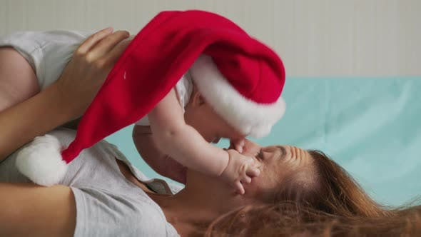 Thumbnail for Funny Little Baby Whit Mother Smiling. Cute Infant Girl Wearing Santa Hat Lying on Sofa