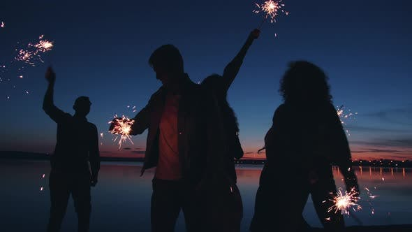 Silhouettes of Men and Women Holding Sparklers Moving Dancing on Lake Shore at Night