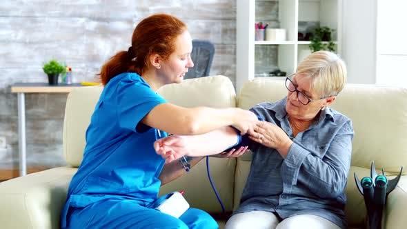 Thumbnail for Female Doctor Taking Blood Pressure of Senior Woman