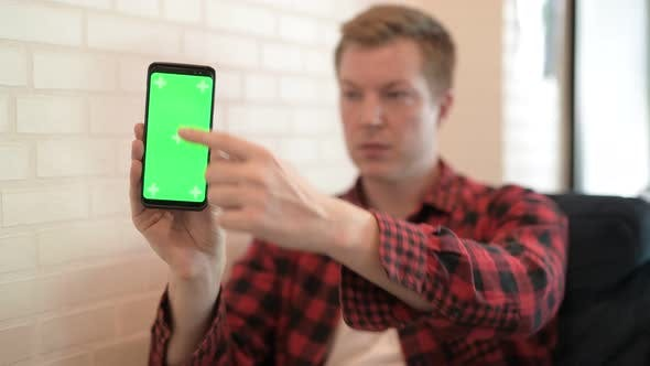 Thumbnail for Young Happy Hipster Man Showing And Using Phone