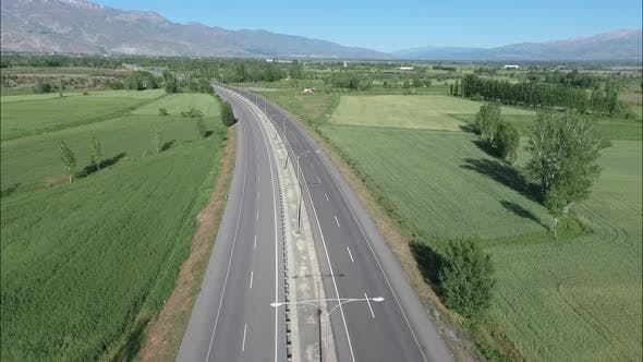 Thumbnail for Aerial Flying Under An Empty Road Through Green Landscape