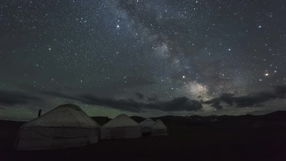 Milky Way Is Moving Across Starry Sky with Clouds Over Yurt Camp