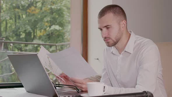 Young Businessman Compares Indicators on Papers