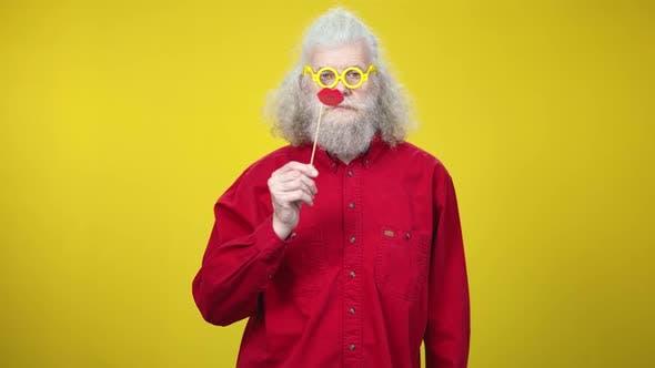 Thumbnail for Joyful Senior Retiree in Yellow Eyeglasses Posing with Toy Lips and Waving at Camera