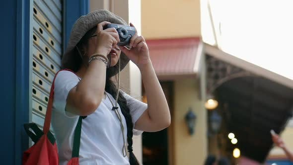 Young Asian woman traveler taking photos around at the market.