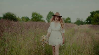 Boho Woman Walking on a Meadow in Summer