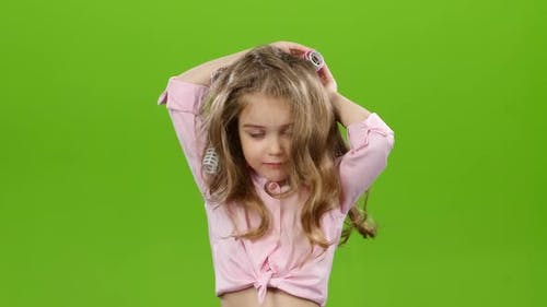Child with Curlers on His Head, Removes Curlers. Green Screen. Time Laps