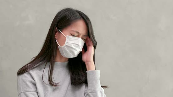 Thumbnail for Frau trägt Maske und Gefühl Kopfschmerzen
