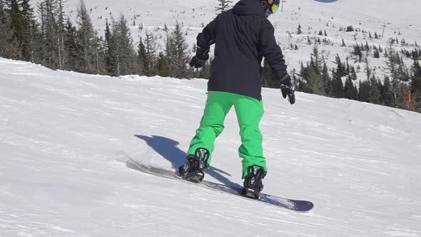 Thumbnail for Snowboarder in a Green-Black Suit on a Ski Slope
