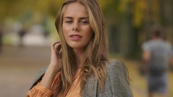 Cover Image for Close-up Portrait of Beautiful Caucasian Woman Standing in Autumn Park and Tucking Hair
