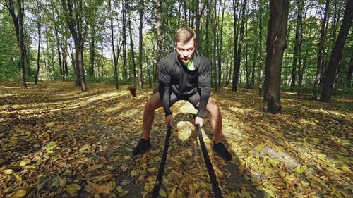 Man with battle ropes. Strong man exercising with battle ropes in park