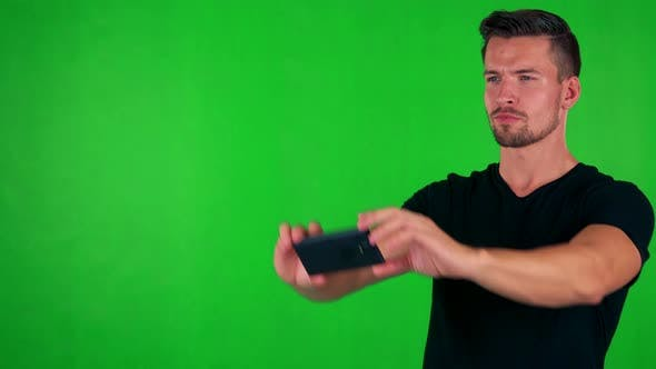 Thumbnail for Young Handsome Caucasian Man Takes Photos Wirh Smartphone - Green Screen