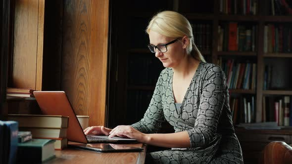 Cover Image for Business Woman in Glasses Works with a Laptop in a Library or a Luxurious Office. In the Background