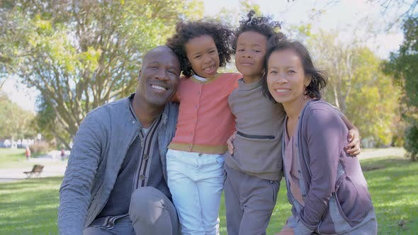 Cover Image for Cheerful Interracial Parents and Kids Posing in Park in Slow Motion