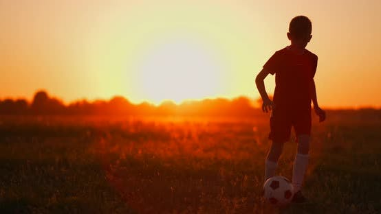 Thumbnail for A Boy with a Football Runs To the Camera at Sunset