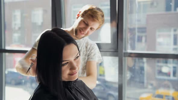 Thumbnail for Male Hairdresser Smiling and Talking with a Customer While Making a New Haircut To Beutiful Young