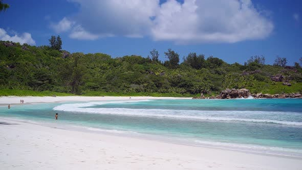 Thumbnail for Anse Coco Beach on La Digue, Seychelles. Unrecognized Tourist Swimming in Shallow Blue Ocean Lagoon