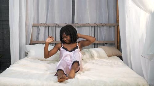 Smiling African American Lady Wakes Up and Stretches on Bed