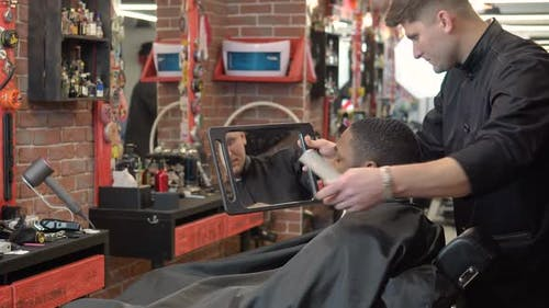 The Hairdresser Shows the Client the Result of the Haircut and Shave in the Hand Mirror