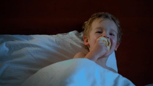 Boy Eating in Bed