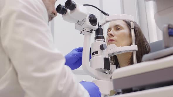 Eye Care Specialist Examining Retina of Female Patient with Slit Lamp