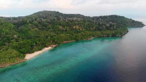 Aerial: flying over Hatta island white sand beach Banda Islands Indonesia