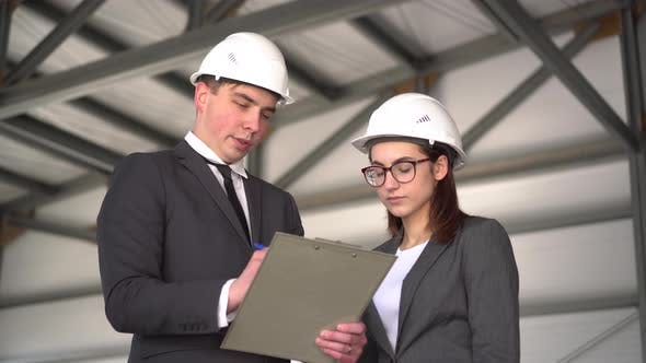 Thumbnail for The Woman Does Not Approve the Project. Young Man and Woman in Helmets with Documents at a
