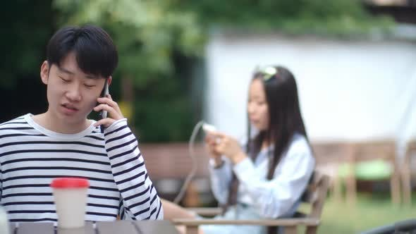 Cover Image for Asian Teen Boy Talking on Cell Phone at Cafe Table Outdoors