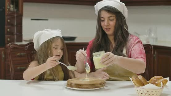 Thumbnail for Caucasian Mother and Daughter Applying Condensed Milk on Baked Cake. Happy Family in Cook Hats and
