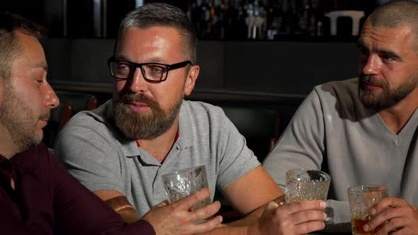 Thumbnail for Group of Mature Male Friends Laughing and Talking Over Glass of Whiskey at the Bar