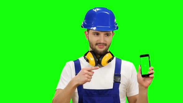Thumbnail for Man in a Builder's Suit Advertises a Smartphone. Green Screen. Mock Up